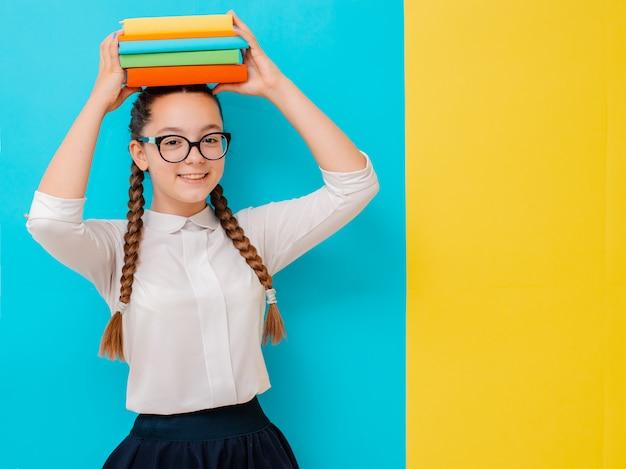 Portret van een schoolmeisje in glazen met boekenhandboeken op geel blauw