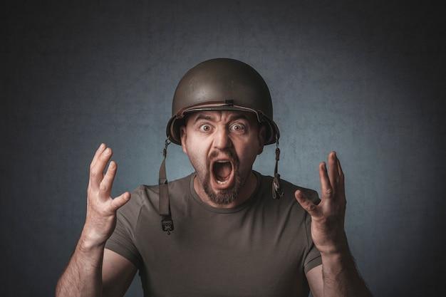 Portret van een schreeuwende soldaat met open armen.
