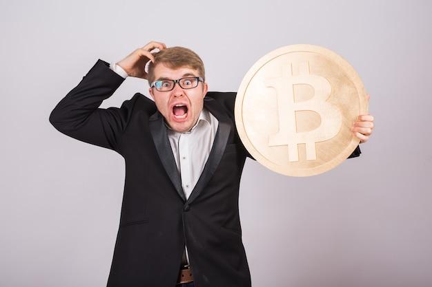 Portret van een schreeuwende zakenman houdt grote gouden bitcoin in zijn armen. man in paniek door crash van cryptocurrency.