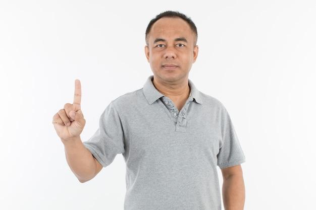 Portret van een senior aziatische man van middelbare leeftijd in een lichtgrijze doek die één vinger opheft en laat zien. isoleer op witte achtergrond.