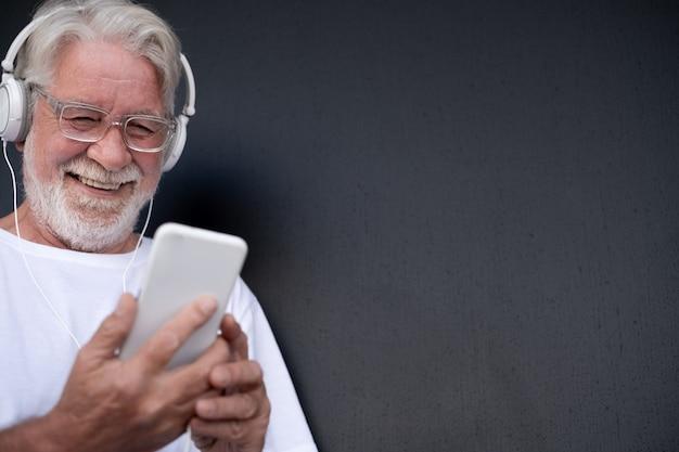 Portret van een senior bebaarde man die lacht terwijl hij naar muziek luistert met een smartphone witte koptelefoon