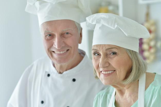 Portret van een senior chef-koks koppel in de keuken