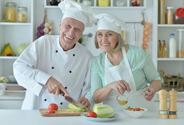 Portret van een senior koppel aan het koken in de keuken