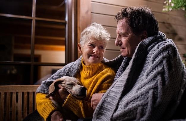 Portret van een senior koppel met een hond die 's avonds op het terras zit gewikkeld in een deken, pratend