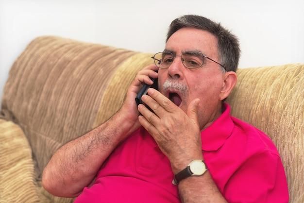 Portret van een senior man geeuwen, praten aan de telefoon. saai gesprek.