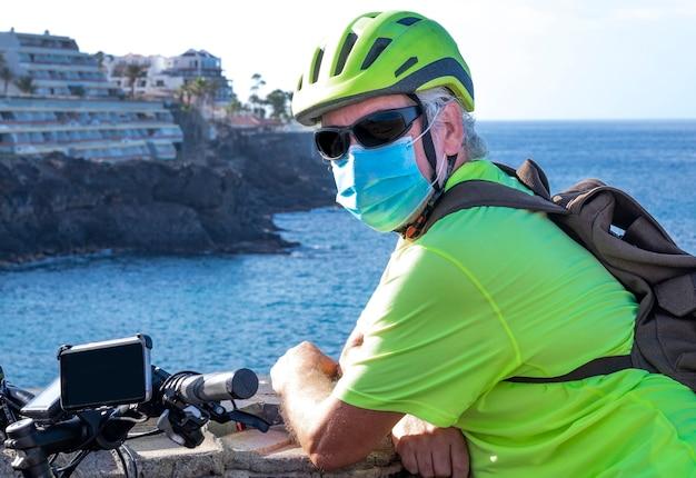 Portret van een senior man met fiets en helm in sportactiviteit genietend van de natuur en de zee