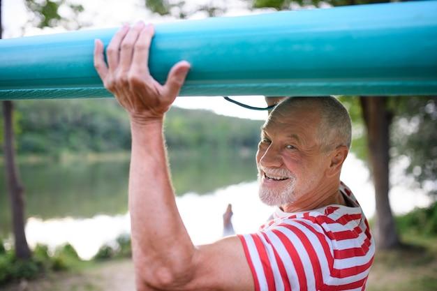 Portret van een senior man met paddleboard aan het meer in de zomer, kijkend naar de camera.