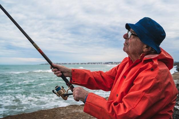 Portret van een senior man vissen in de zee, genieten van het leven. visserij en sport concept.