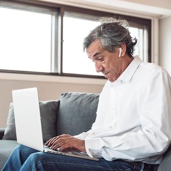Portret van een senior man zittend op de bank dragen van bluetooth oortelefoon met behulp van laptop