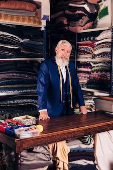 Portret van een senior mannelijke modeontwerper in zijn kledingwinkel