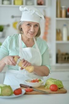 Portret van een senior vrouw chef-kok portret in de keuken