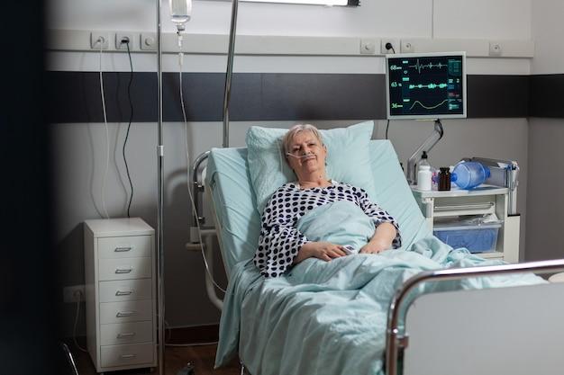 Portret van een senior vrouw die lacht en naar een camera kijkt die in een ziekenhuisbed ligt, een behandeling met een infuuszak. ademen met behulp van zuurstofmasker tijdens ziekteherstel.