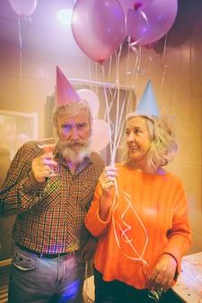 Portret van een senior vrouw met ballonnen in de hand te kijken naar haar man met martin glas