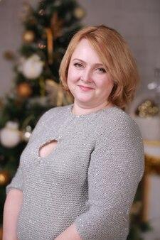 Portret van een senior vrouw poseren in de buurt van kerstboom.