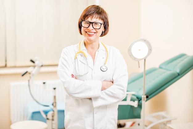 Portret van een senior vrouwelijke gynaecoloog die op kantoor staat met gynaecologische stoel en lamp op de achtergrond