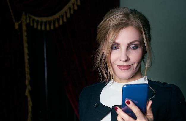 Portret van een senior zakenvrouw draagt formele pak praten over een telefoon