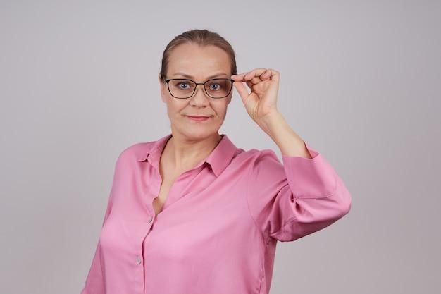 Portret van een senior zakenvrouw in een roze blouse met de boog van haar bril met haar hand. geïsoleerde foto op een grijze achtergrond met kopie ruimte.