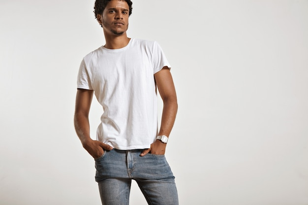 Portret van een sensueel zwart jong model in een wit t-shirt zonder label, een lichtblauwe spijkerbroek en een vintage digitaal horloge