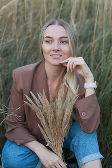 Portret van een sensuele blonde jonge vrouw in tarwe op een zomeravond. het meisje koestert een bos tarwe.