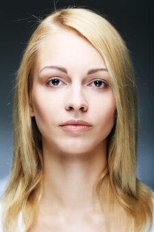 Portret van een sensuele jonge blonde vrouw die op wit wordt geïsoleerd