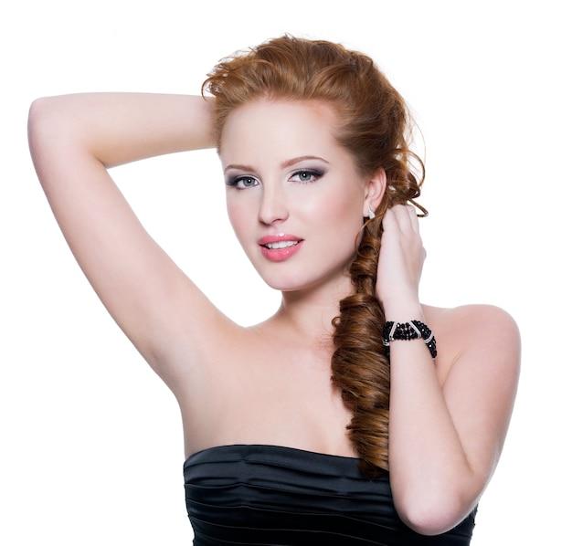 Portret van een sensuele jonge roodharige vrouw met heldere glamoursamenstelling op witte muur