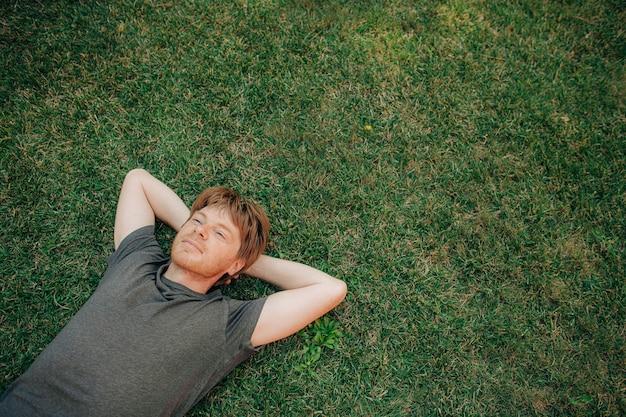 Portret van een serene volwassen man die op het gras ligt