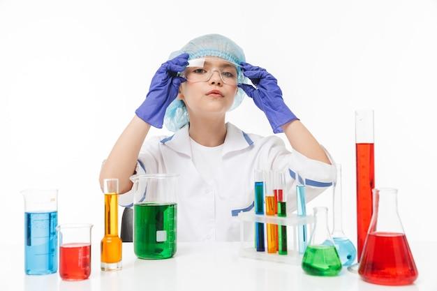 Portret van een serieus klein meisje in een witte laboratoriumjas die chemische experimenten maakt met veelkleurige vloeistof in reageerbuisjes geïsoleerd over een witte muur