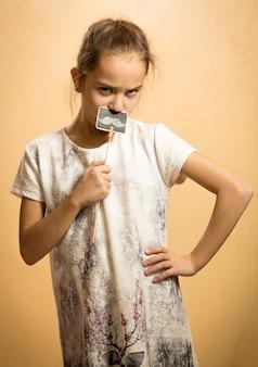 Portret van een serieus meisje dat speelt met decoratieve snorren