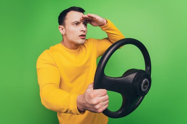 Portret van een serieuze, avontuurlijke kerel die het stuur van de palm van het voorhoofd vasthoudt, ziet er lege ruimte uit op een groene achtergrond