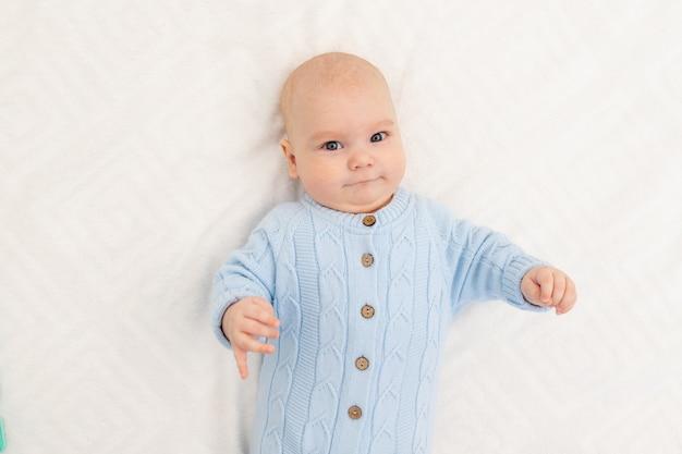 Portret van een serieuze babyjongen op het bed voordat hij naar bed gaat of de ochtend van de baby
