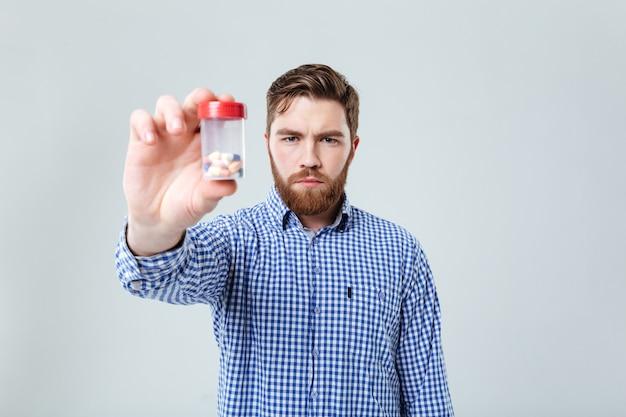 Portret van een serieuze bebaarde jonge man die een fles pillen over een witte muur laat zien
