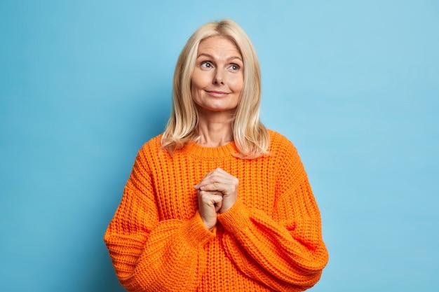Portret van een serieuze dromerige europese dame die ergens geconcentreerd is en de handen bij elkaar houdt, herinnert aan iets aangenaams gekleed in een oversized gebreide oranje trui.