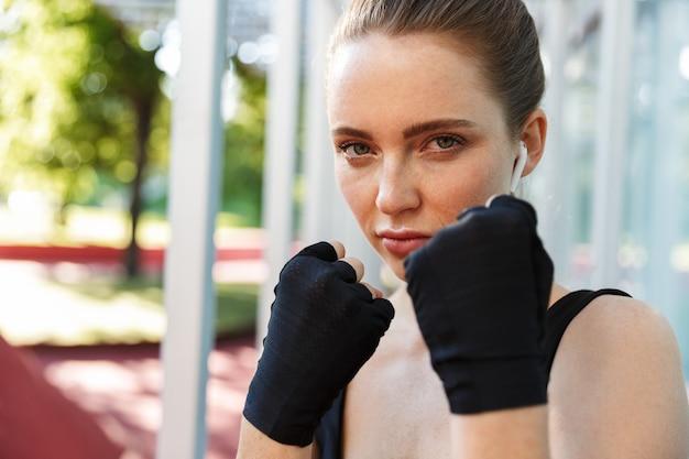 Portret van een serieuze jonge vrouw die een trainingspak draagt en haar sportieve handschoenen laat zien terwijl ze aan het trainen is op een sportveld in een groen park