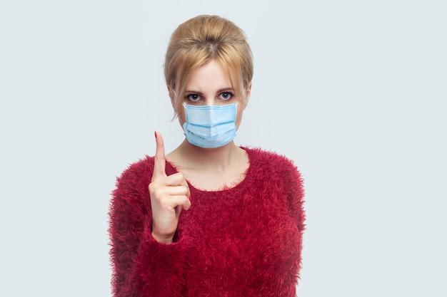 Portret van een serieuze jonge vrouw met een chirurgisch medisch masker in een rode blouse die staat en naar de camera kijkt met een waarschuwende vinger en alarmerend over de gezondheidszorg. binnen schot geïsoleerd op een grijze achtergrond.