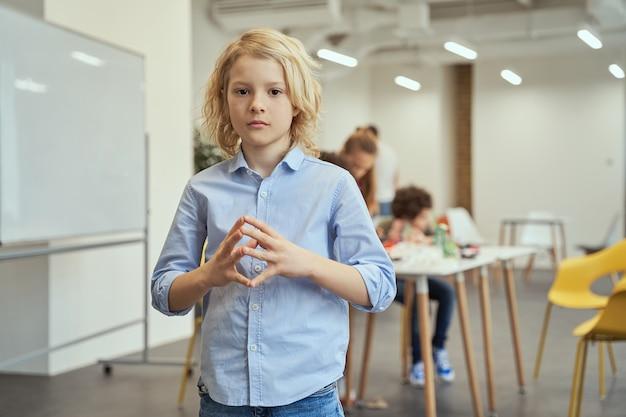 Portret van een serieuze jongen die naar de camera kijkt en een handgebaar van de toren laat zien terwijl hij voor de camera poseert