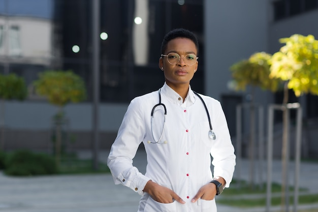 Portret van een serieuze kinderarts-doktervrouw in de buurt van de kliniek in een medische toga