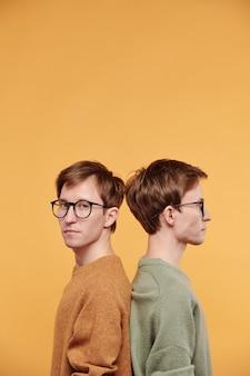 Portret van een serieuze knappe jongeman met een bril die rug aan rug staat met tweelingbroer tegen een lichte achtergrond