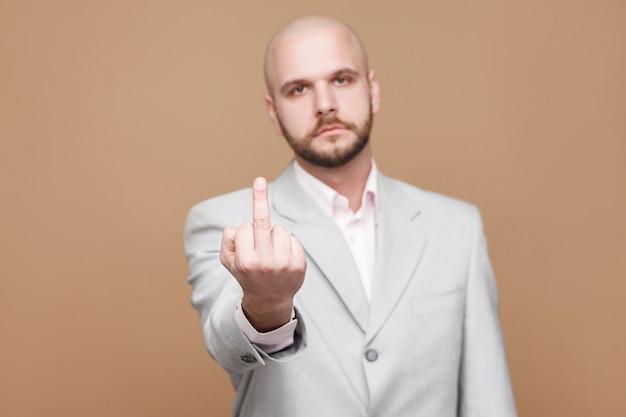Portret van een serieuze, knappe, kale, bebaarde zakenman van middelbare leeftijd in een klassiek lichtgrijs pak die naar de camera kijkt en middelvinger toont met pokerface. studio-opname op lichtbruine achtergrond