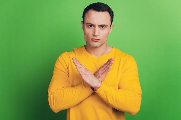 Portret van een serieuze man maakt een verbodsbord met gekruiste handpalmen op een groene achtergrond
