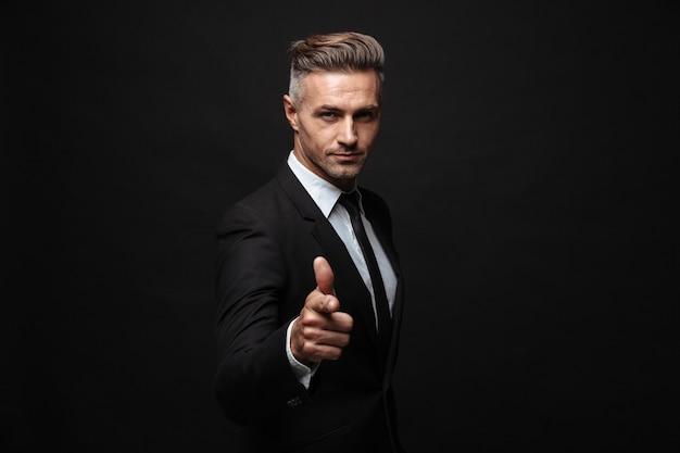 Portret van een serieuze mannelijke zakenman gekleed in een formeel pak wijzend met de vinger en kijkend naar camera geïsoleerd over zwarte muur