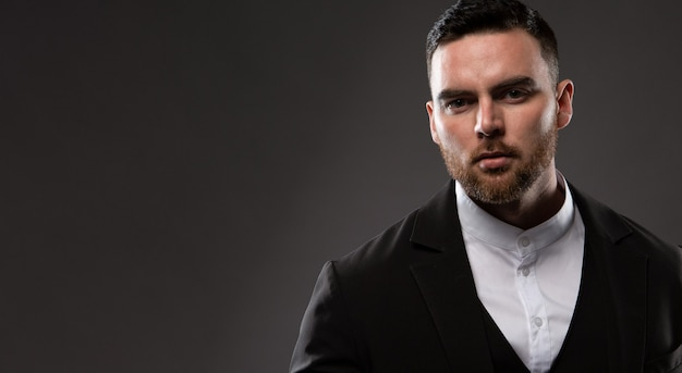 Portret van een serieuze mode-zakenman met een baard, gekleed in een zwart pak en een wit overhemd