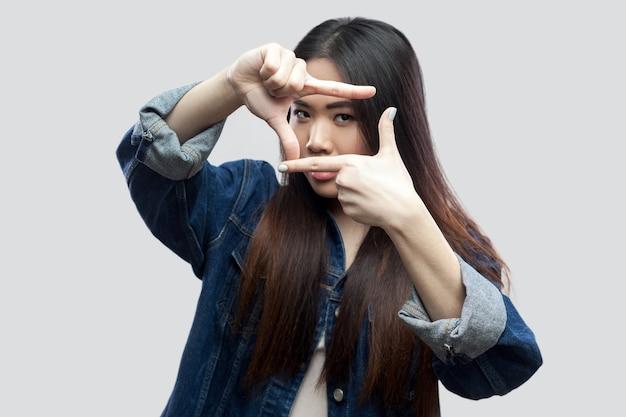 Portret van een serieuze, mooie brunette aziatische jonge vrouw in een blauw spijkerjasje met make-up die staat en naar de camera kijkt met een gebaar van de gewassamenstelling. studio opname, geïsoleerd op lichtgrijze achtergrond.