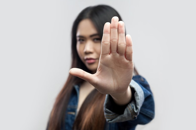 Portret van een serieuze, mooie brunette aziatische jonge vrouw in een casual blauw denim jasje, make-up die met een stophandteken staat en naar de camera kijkt. studio opname, geïsoleerd op lichtgrijze achtergrond.