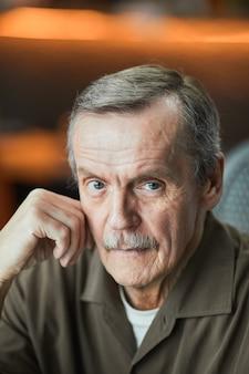 Portret van een serieuze senior blanke man met grijze snor en rimpels die met het hoofd op de hand leunen