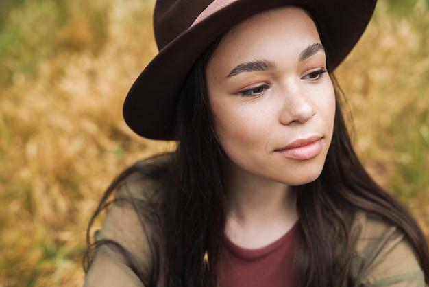 Portret van een serieuze stijlvolle vrouw met lang donker haar met een hoed die opzij kijkt terwijl ze buiten op het gras zit