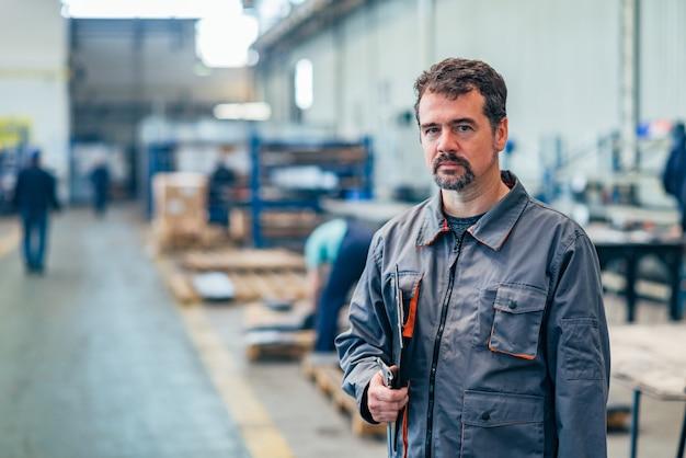 Portret van een serieuze technicus in de fabriek.