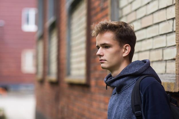 Portret van een serieuze tiener tegen een bakstenen muur