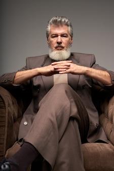 Portret van een serieuze volwassen zakenman met een baard die een elegant pak draagt en naar de camera kijkt