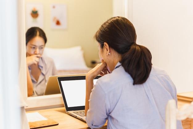 Portret van een serieuze vrouw die aan laptop in hotelkamer werkt.