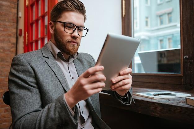 Portret van een serieuze zakenman die aan tafel zit en tabletcomputer vasthoudt
